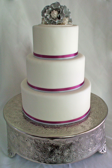 3 tier white fondant round wedding cake with purple and silver ribbons and silver southern magnolia flowers hilighted with purple pearl dust