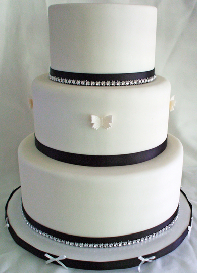 3 Tier round white fondant wedding cake decorated with black and diamond bling ribbons and white butterflies