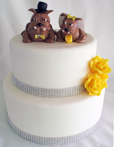 2 Tier fondant wedding cake, decorated with bling diamond ribbons, yellow chocolate roses and custom handmade bull dog bride and groom