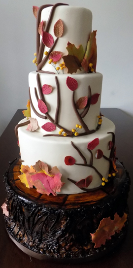 4 Tier fondant wedding cake, decorated with fall leaves and brown vines with the bottom tier designed to look like a tree stump. Fondant wedding cakes York PA