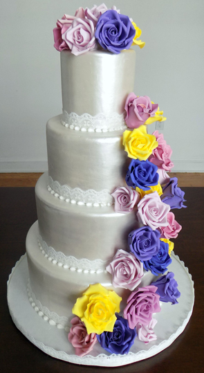 4 Tier metallic wedding cake, decorated with lace ribbons and cascading sugar roses in assorted spring colors