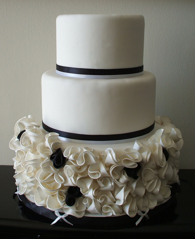 3 Tier round white fondant wedding cake decorated with black and white ribbons and black and white ruffle flowers with silver painted edges