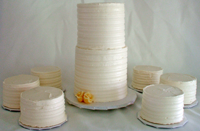 Tiered mini wedding cake with individual size wedding cakes, iced in vanilla buttercream and decorative combed sides